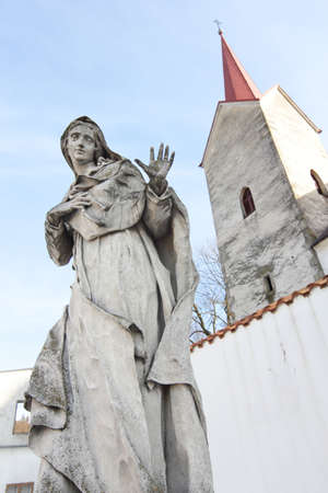 Granite statue of Virgin Mary with church tower Stock Photo - 18569741