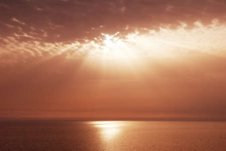 Puesta del sol los rayos y las nubes sobre el mar por la noche Foto de archivo