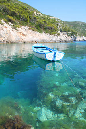Romantic boat with painted hearts floating on transparent sea water photo