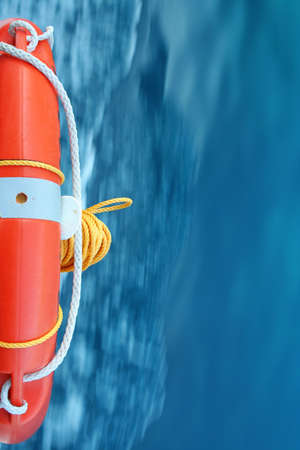 Red Lifebuoy with blue sea water flowing in the background Stock Photo - 21948299