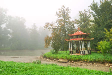 Small eastern arbour on a lake island in a foggy morning photo