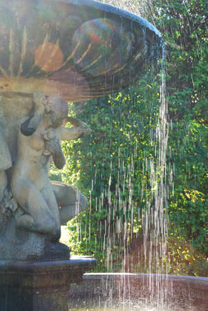 Baroque girl statue with fountain water falling down in sunlight photo