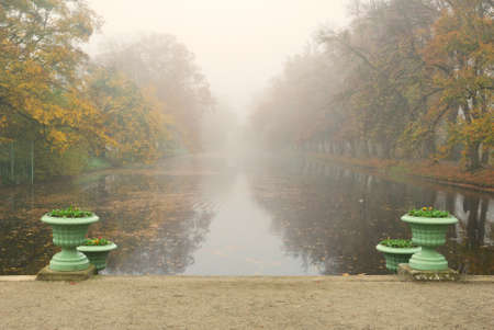 Long park pond in foggy autumn morning photo