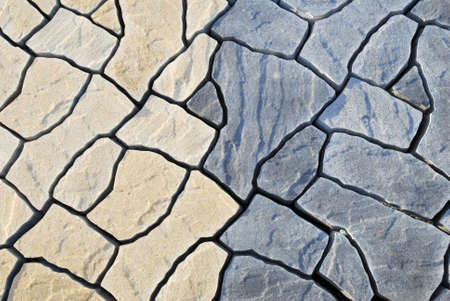 Abstract background paving consisting of irregular stones of two colors in top view photo