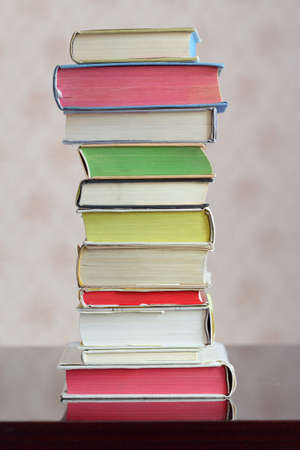 hardback: A column of hardback colorful closed books on a table Stock Photo