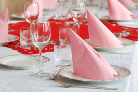 Catering table arranged with silverware and pink napkins and tables photo