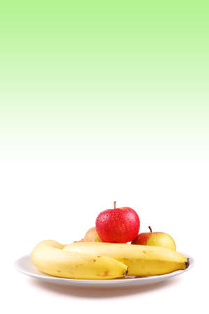 Fresh bananas and apples on a white porcelain plate photo