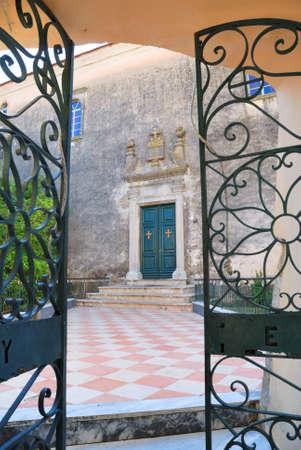 Greek monastery and opened iron ornamental gate photo
