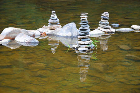 Towers of small pebbles in the middle of a shallow river photo