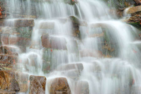 Water flowing over rocks in waterfall cascade in a forest photo