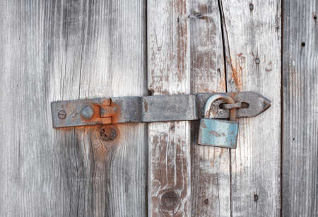 Old wooden door secured by rusty padlock photo