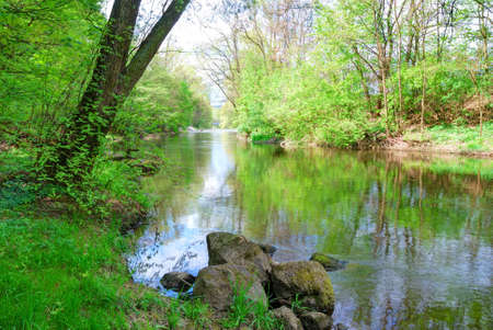 Small river and green banks in springtime Stock Photo