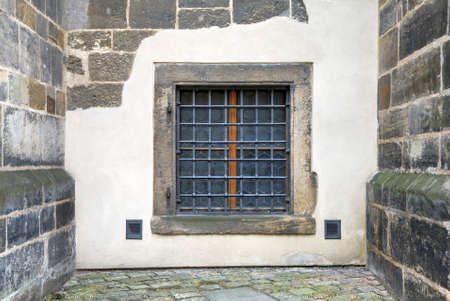 part prison: Window with bars set in an old fortress stone wall