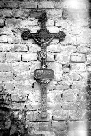 Rusty christian cross with Jesus Christ statue hanging on an old brick wall