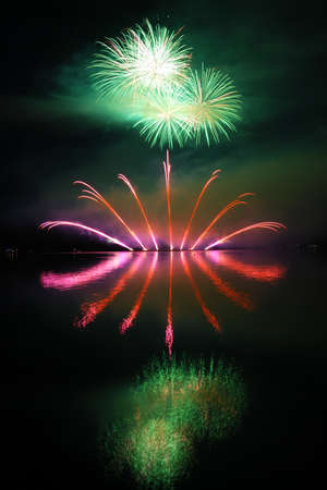 Colorful spectacular fireworks with reflections in the water photo