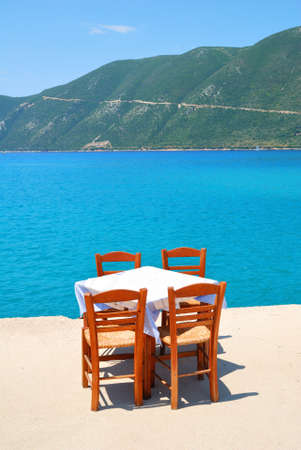 seafront: Dining table with chairs in a greek taverna with blue sea and green hills