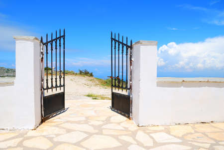 iron gate: Opened iron gate in a white wall with blue sky behind