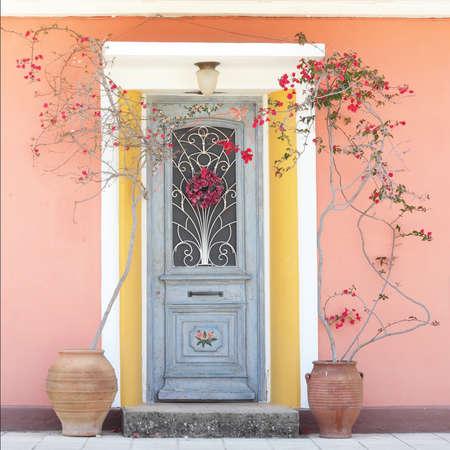 Hermosa casa acogedora puerta decorativa con flores rosas rojas Foto de archivo