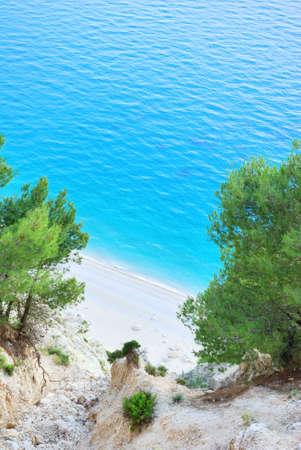 Beautiful beach under a high cliff with light blue sea