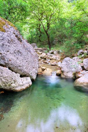 Clean creek water pool with big rocks photo