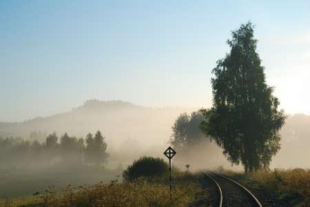 Empty railway track in a foggy countryside photo