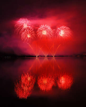 Beautiful red fireworks reflecting in water photo