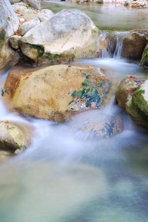 Clear water flowing over rocks into a small pool photo