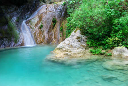 Natural pool with azure water and a small waterfall Stock Photo