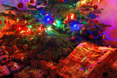 Many wrapped presents under a lit Christmas tree photo