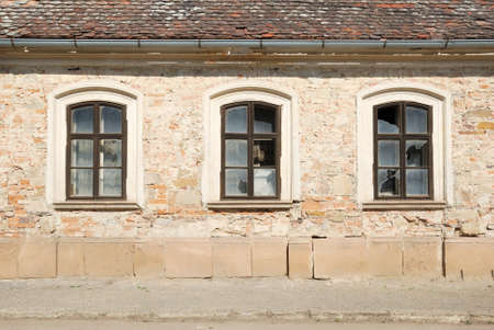 damaged house: Three broken windows in a wall of a damaged house