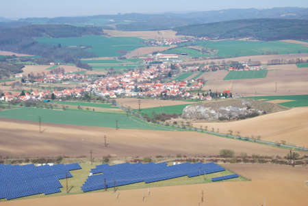 solar array: Early spring landscape with brown fields and solar power plant array
