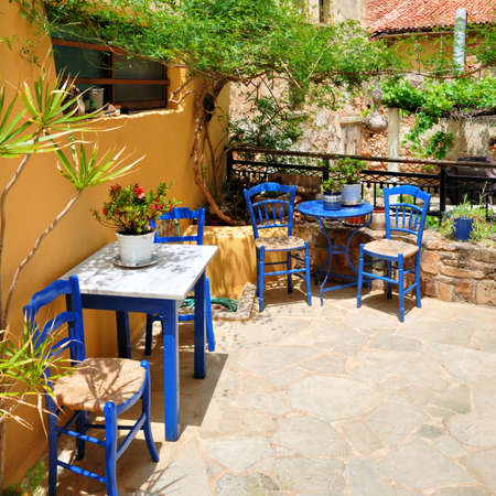 Traditional blue greek chairs in a beautiful backyard photo