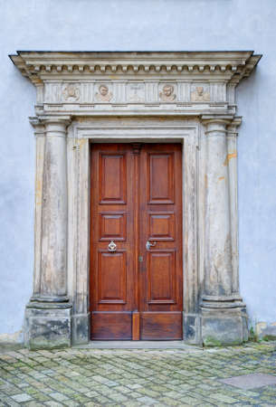 Old monastery portal and brown wooden door photo