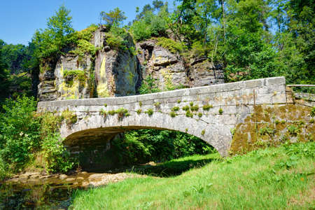 rivulet: Old stone bridge over a small rivulet in summer season