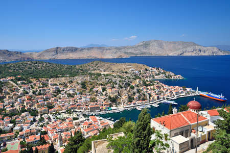 Symi island colorful town houses and harbour with ships, Greece Stock Photo