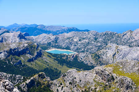High mountains range with a blue lake on the island of Mallorca Stock Photo