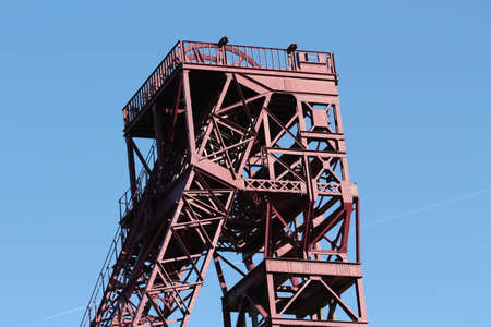 Red mining tower in front of blue sky Фото со стока