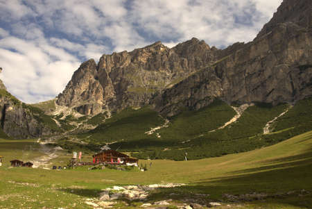 Alpine hut surrounded by mountain pastures in front of Alpine panorama
