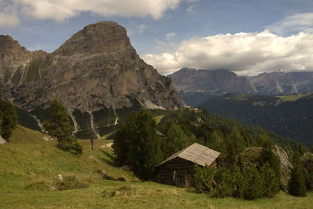 Mountain landscape with high mountains, meadows and forest, in the foreground below a mountain hut Фото со стока