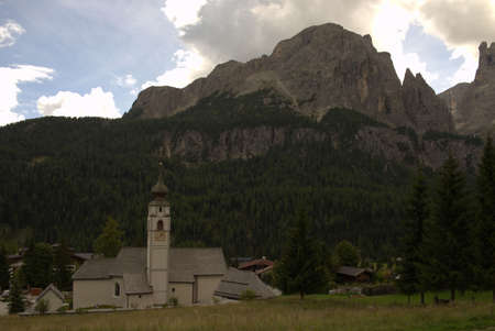 White church in front of high mountain range in the Italian Dolomites