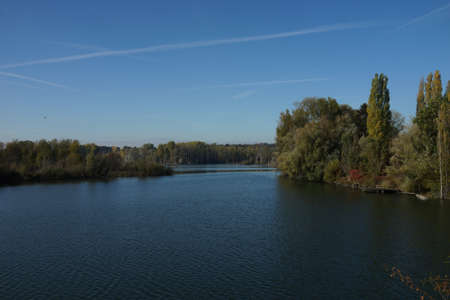 View over a still-lying lake with a wooded shore Фото со стока