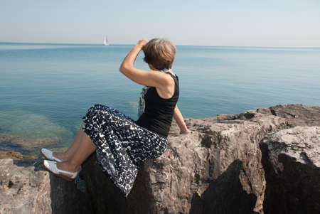 vastness: The slender woman on the Lake Michigan shore watches for sailing vessel Stock Photo