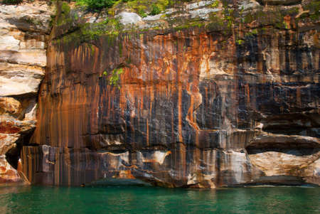 pictured: Mineral colored sandstone on the cliffs Pictured Rocks National Lakeshore, Michigan, USA