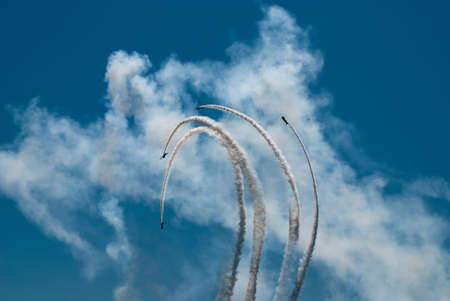 manoeuvre: Four airplane perform aerobatic manoeuvre in the blue sky