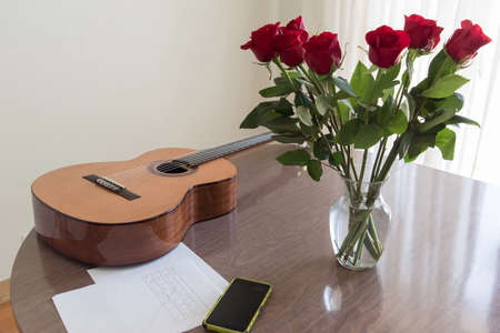 Still life with a guitar, a bouquet of roses, a smartphone and musical notes