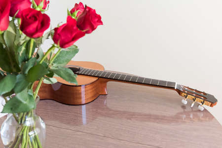 Still life with a bouquet of roses and a guitar Stock Photo