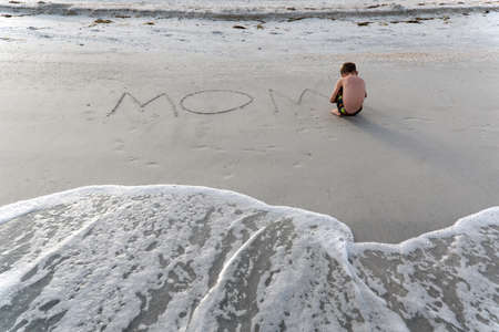 grader: A little boy writes on the beach sand the word Stock Photo