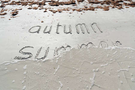 Waves wash away the word summer on the sand of the beach. Goodbye Summer! Hello, Autumn!  Stock fotó
