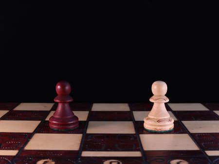 Two hand-decorated, wooden, chess figurines are standing on a chessboard.