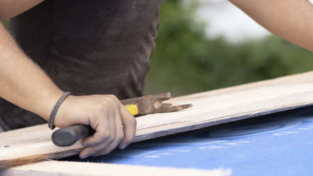 The worker is preparing a batten for nailing to the roof. Stock Photo
